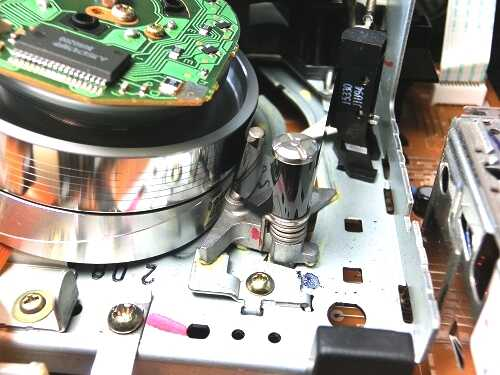 VHSビデオデッキ内部の供給側ローディングアームにテープがかかっている様子